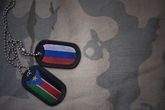 army blank, dog tag with flag of russia and south sudan on the khaki texture background. Stock Photo
