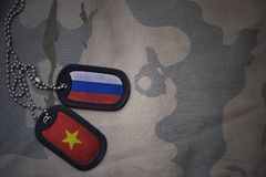 Army blank, dog tag with flag of russia and vietnam on the khaki texture background. Military concept Stock Image