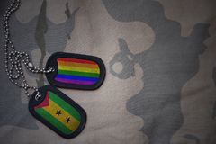 Army blank, dog tag with flag of sao tome and principe and gay rainbow flag on the khaki texture background. Military concept Stock Photography