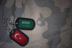Army blank, dog tag with flag of saudi arabia and turkey on the khaki texture background. Military concept stock images