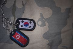 Army blank, dog tag with flag of south korea and north korea on the khaki texture background. Military concept stock photo