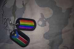army blank, dog tag with flag of south sudan and gay rainbow flag on the khaki texture background. Stock Illustration