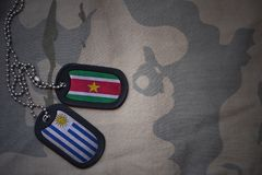 Army blank, dog tag with flag of suriname and uruguay on the khaki texture background. Military concept Royalty Free Stock Images