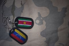 Army blank, dog tag with flag of suriname and venezuela on the khaki texture background. Military concept Stock Image