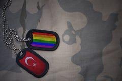 Army blank, dog tag with flag of turkey and gay rainbow flag on the khaki texture background. Stock Photos