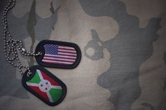Army blank, dog tag with flag of united states of america and burundi on the khaki texture background. Stock Photos