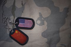 Army blank, dog tag with flag of united states of america and china on the khaki texture background. Military concept Stock Photo