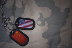 Army blank, dog tag with flag of united states of america and china on the khaki texture background. Military concept Royalty Free Stock Images