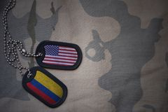 Army blank, dog tag with flag of united states of america and colombia on the khaki texture background. Stock Photos