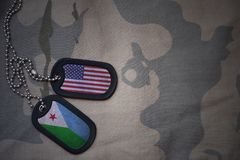 Army blank, dog tag with flag of united states of america and djibouti on the khaki texture background. Stock Photo