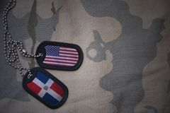 Army blank, dog tag with flag of united states of america and dominican republic on the khaki texture background. Stock Image
