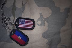 Army blank, dog tag with flag of united states of america and haiti on the khaki texture background. Military concept stock photography