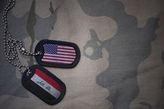 Army blank, dog tag with flag of united states of america and iraq on the khaki texture background. Stock Photo