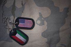 Army blank, dog tag with flag of united states of america and kuwait on the khaki texture background. Military concept Stock Image