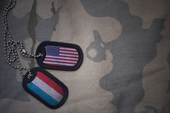 Army blank, dog tag with flag of united states of america and luxembourg on the khaki texture background. Military concept Stock Photography