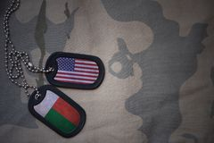 Army blank, dog tag with flag of united states of america and madagascar on the khaki texture background. Military concept Royalty Free Stock Photography