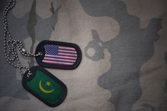 Army blank, dog tag with flag of united states of america and mauritania on the khaki texture background. Royalty Free Stock Images