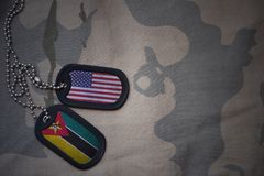 Army blank, dog tag with flag of united states of america and mozambique on the khaki texture background. Stock Photography