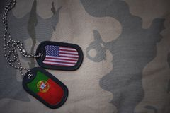 Army blank, dog tag with flag of united states of america and portugal on the khaki texture background. Stock Photo