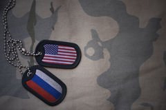 Army blank, dog tag with flag of united states of america and russia on the khaki texture background. Military concept royalty free stock photography