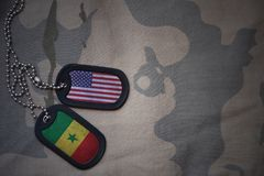 Army blank, dog tag with flag of united states of america and senegal on the khaki texture background. Stock Image