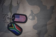 Army blank, dog tag with flag of united states of america and south africa on the khaki texture background. Royalty Free Stock Photo