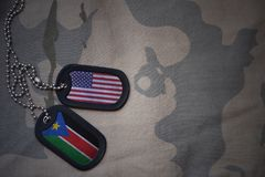 Army blank, dog tag with flag of united states of america and south sudan on the khaki texture background. Stock Image