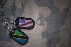 Army blank, dog tag with flag of united states of america and tanzania on the khaki texture background. Stock Photography
