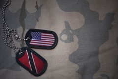 Army blank, dog tag with flag of united states of america and trinidad and tobago on the khaki texture background. Stock Photos