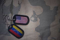 Army blank, dog tag with flag of united states of america and venezuela on the khaki texture background. Stock Photography