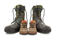 Army boots and children's shoes Royalty Free Stock Images