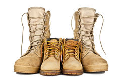 Army boots and children's shoes Royalty Free Stock Photography