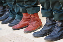 Army Boots Stand Out in a Crowd. An army soldier wears brown boots while all other soldiers wear traditional black boots while participating in a military parade Royalty Free Stock Photos