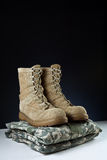 Army Combat Boots - Uniform Angle. Angled photo of a apir of tan leather Army combat boots placed together on camouflage uniform on black background Stock Photo
