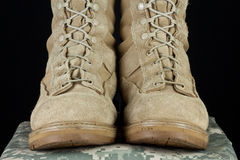 Army Combat Boots - Uniform Straight. Pair of tan leather Army combat boots placed together on camouflage uniform on black background Royalty Free Stock Photo