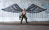 Army girl with rifle with angel wings. Beautiful army girl with rifle in camouflage clothes in front of angel wings graffiti on the wall Royalty Free Stock Photo