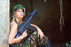 Army girl with rifle. Beautiful army girl with rifle in camouflage clothes Royalty Free Stock Image