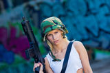 Army girl with rifle. Beautiful army girl with rifle in camouflage clothes in urban scene Royalty Free Stock Photo