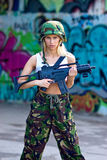 Army girl with rifle. Beautiful army girl with rifle in camouflage clothes in urban scene Royalty Free Stock Image