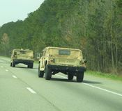 Army hummers driving down the interstate stock images
