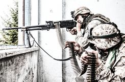 Army machine gunner attacks enemy with aimed fire. Marine Corps machine gun crew shooting through window in ruined building during city firefight. Army machine stock photo
