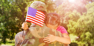 Army man hugging daughter with American flag. Rear view of army men hugging daughter with American flag while leaving from home Royalty Free Stock Photo