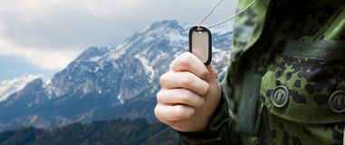 Close up of young soldier with military badge. Army, national service and people concept - close up of young soldier military badge over mountains background Royalty Free Stock Image