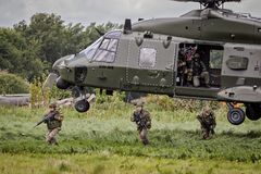 Army NH90 helicopter soldiers disembark. BEAUVECHAIN, BELGIUM - MAY 20, 2015: Soldiers disembark from an army NH90 helicopter Royalty Free Stock Photo