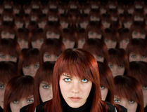 Army of one. Beautiful redhead girl with piercing and hundred clones staring at camera Stock Photography