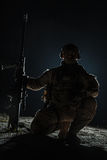 Army sniper with big rifle sitting. Holding rifle on black background Royalty Free Stock Photography