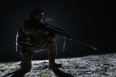 Army sniper with big rifle sitting holding rifle Stock Photo