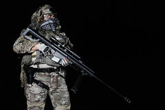 Army sniper with big rifle standing. On black background Stock Photography