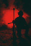 Army sniper in the fire and smoke. Army sniper with large caliber rifle sitting in the fire and smoke. Backlit silhouette, toned image Royalty Free Stock Image