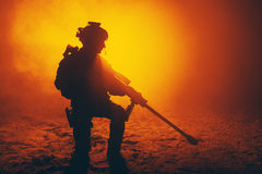Army sniper in the fire and smoke. Army sniper with large caliber rifle sitting in the fire and smoke. Backlit silhouette, toned image Stock Photography